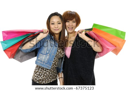 Portrait of two friends with shopping bags in hands - stock photo
