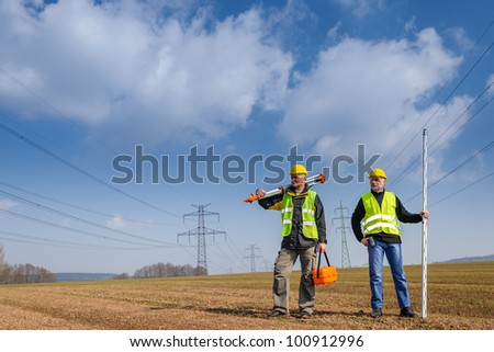 Portrait of two geodesist holding measuring equipment on construction site - stock photo