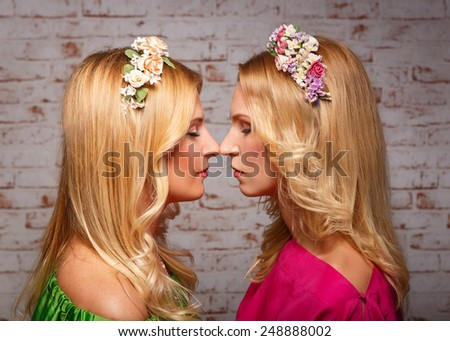 portrait of two girls blondes look at each other. - stock photo