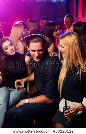Portrait of two girls with cocktails surrounding happy guy in the nightclub