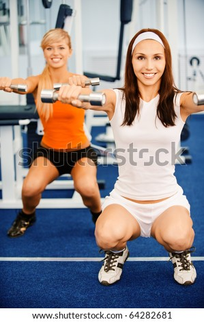 portrait of two girls working out with dumbbells - stock photo