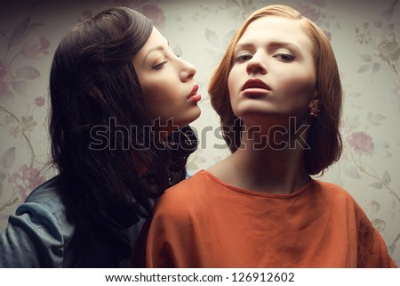 Portrait of two gorgeous girlfriends in blue and orange dresses in a hotel room. Brunette trying to kiss red-haired model. Vintage style. Studio shot