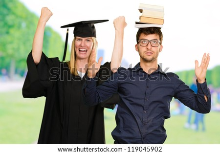 Portrait Of Two Graduate Students, Outdoors - stock photo