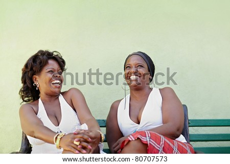 portrait of two happy african adult women talking on bench and smiling. Horizontal shape, copy space - stock photo