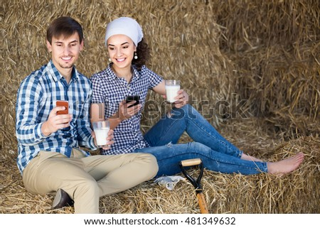 portrait of two happy american farmers taking a pause in the hay and having their phones in hands