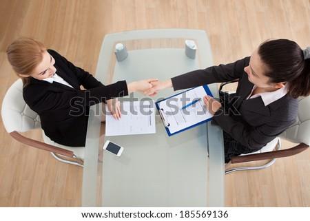 Portrait Of Two Happy Businesswoman Having Handshake In Office - stock photo