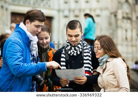 Portrait of two happy couples of tourists reading city map and looking for correct way - stock photo