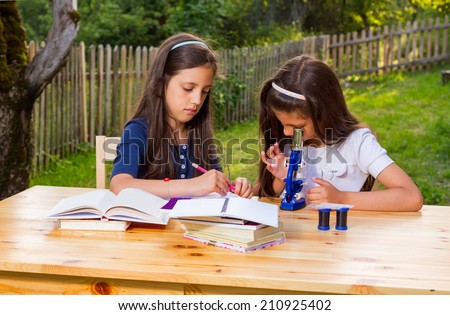 Portrait of two happy female young students on campus sitting casually at an outdoor table.  - stock photo