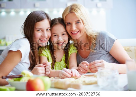 Portrait of two happy girls and their mother cooking pastry together - stock photo