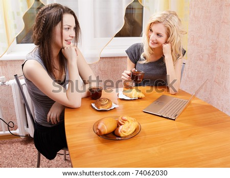 portrait of two happy girls with laptop drinking tea wit buns and rolls