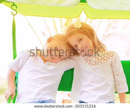 Portrait of two happy kids on swing, enjoying entertainment in summer camp, carefree childhood, active lifestyle, friendly family concept - stock photo