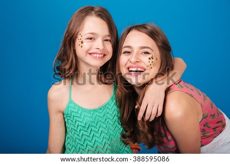 Portrait of two happy lovely sisters with decorations on cheeks laughing over blue background - stock photo