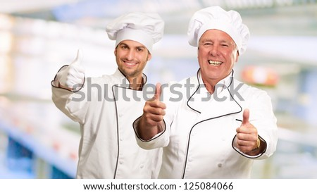 Portrait Of Two Happy Male Chef While Gesturing, Indoors - stock photo