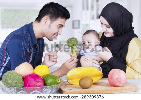 Portrait of two happy parents showing healthy food on their baby in the kitchen