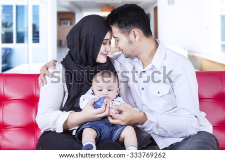 Portrait of two happy parents sitting on the sofa while holding their baby at home - stock photo