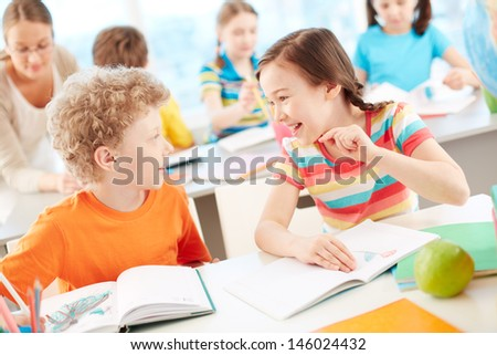 Portrait of two happy pupils interacting at drawing lesson - stock photo