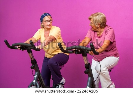 Portrait of two Happy senior girl friends working out on stationary bikes in gym.