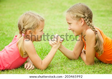Portrait of two happy sister playing on the grass at the day time - stock photo