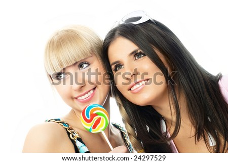 portrait of two happy smiling beautiful girls with a candy