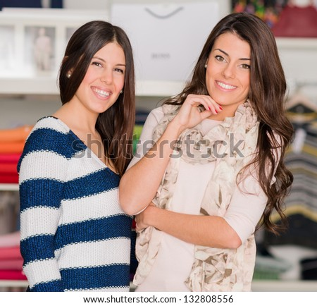 Portrait Of Two Happy Women Standing In Shopping Mall, Indoors