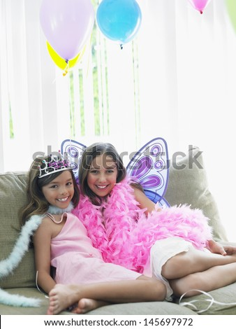 Portrait of two happy young girls sitting on sofa in party costumes - stock photo