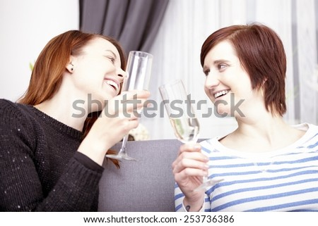 portrait of two happy young girls with champagne at home