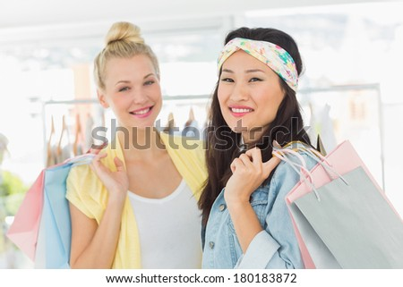 Portrait of two happy young women with shopping bags in the clothes store - stock photo