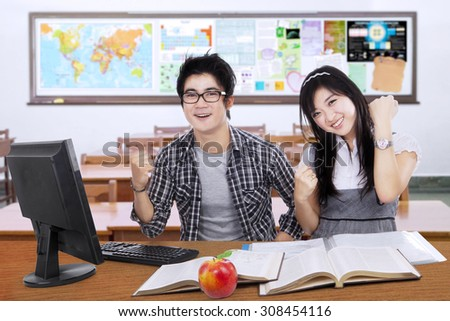 Portrait of two high school students back to school and sitting in the class while expressing success - stock photo