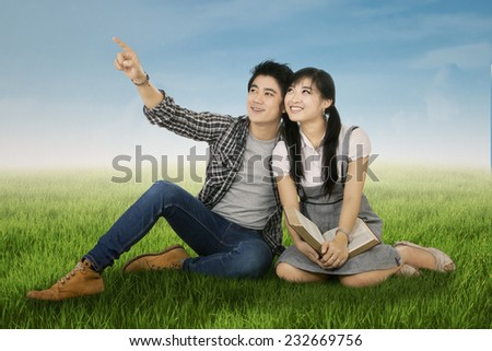 Portrait of two high school students sitting in the park - stock photo