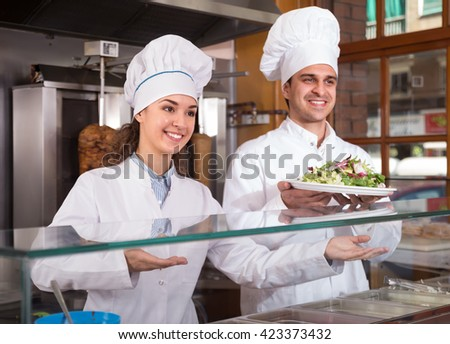 Portrait of two hospitable chefs with kebab at fastfood place