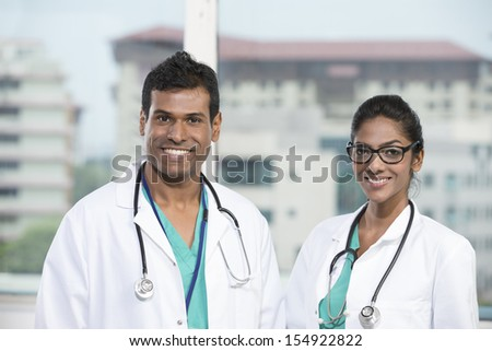 Portrait of two Indian doctors standing with a stethoscope's around there necks  - stock photo