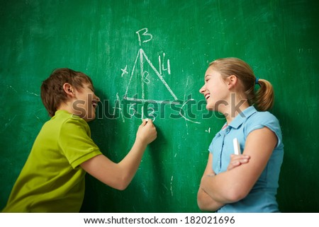 Portrait of two joyful classmates by the blackboard at the lesson of geometry - stock photo