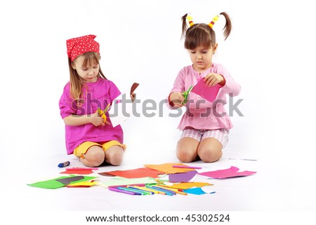 Portrait of two kid girls playing with colored paper