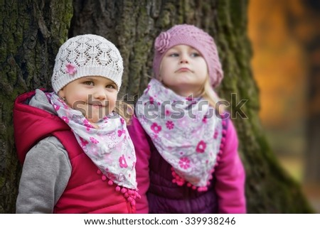 Portrait of two kids in the park with a large tree trunk - stock photo
