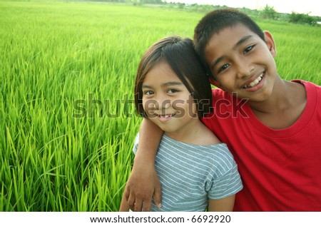 Portrait of two kids in the rice field. - stock photo