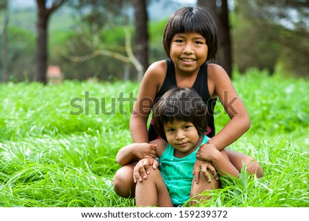 Portrait of two Latin American sisters outdoors. - stock photo