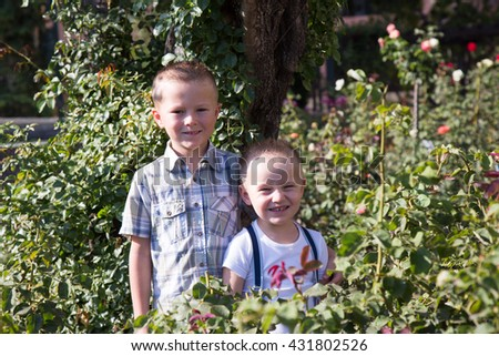 Portrait of two little boys brothers outside.  - stock photo