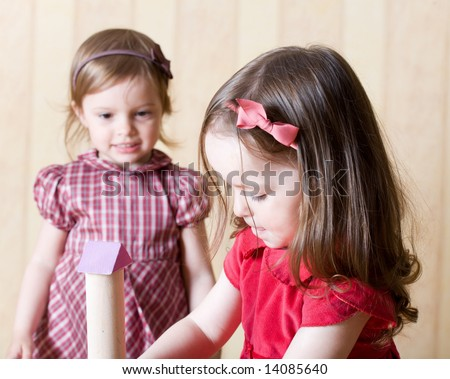Portrait of two little girls building toy tower from wooden bricks at home