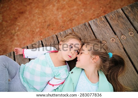 portrait of two little sister who love each other - stock photo