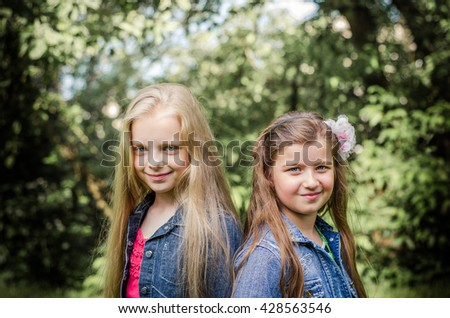Portrait of two long haired preteen girls while smiling. - stock photo