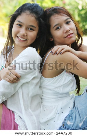 Portrait of two lovely Thai girls sitting back to back - stock photo