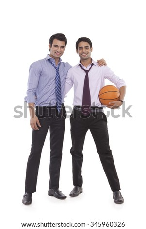Portrait of two male executives with a basketball - stock photo