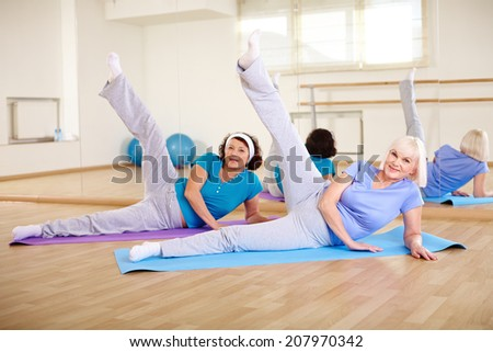 Portrait of two mature females doing physical exercise in sport gym  - stock photo