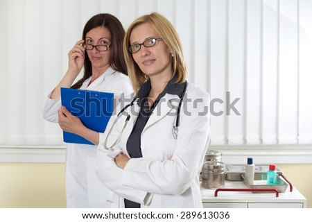 Portrait of Two Medical Colleagues Smiling and Looking at Camera in Consulting Room - stock photo