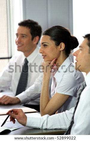 Portrait of two men and a woman smiling at work - stock photo
