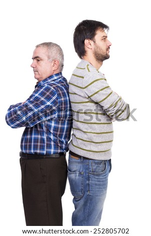 Portrait of two men, father and son, standing back to back with arms folded over white background - stock photo