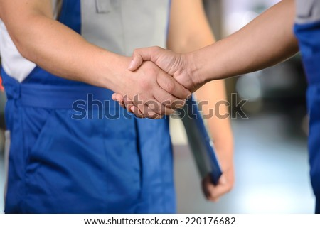 Portrait of two men handshake mechanics in auto repair service - stock photo