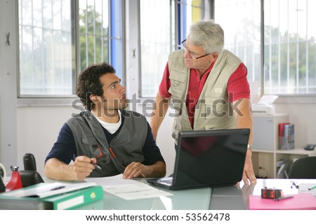 Portrait of two men in front of a laptop computer in an office - stock photo