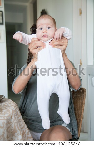 portrait of two month age baby white onesie shirt open eyes funny expression face stretched in hands of brunette woman mother with grey shirt and pigtails sitting indoor - stock photo