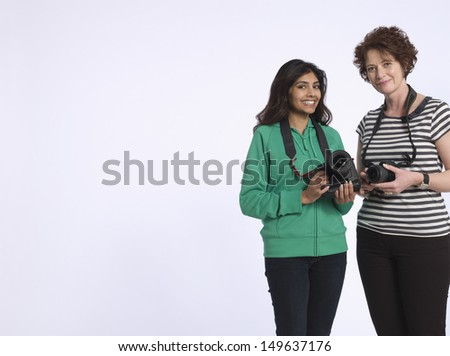 Portrait of two multiethnic women holding digital cameras in studio - stock photo